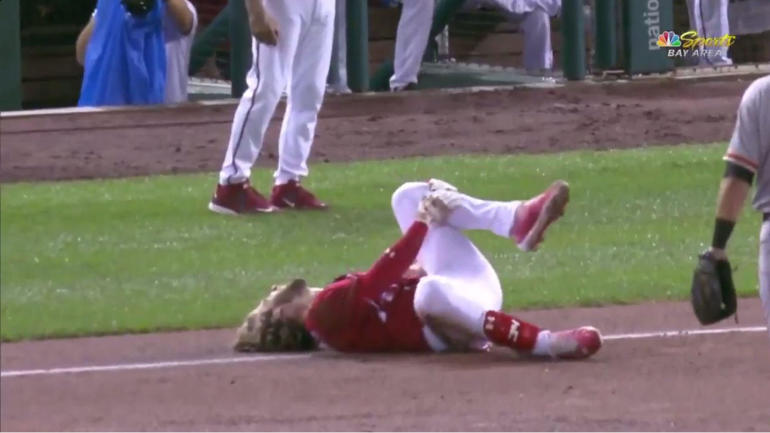 Nationals' Bryce Harper helped off the field after hurting knee slipping on wet base
