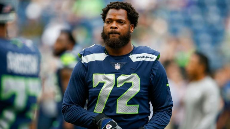 Seahawks' Michael Bennett sits during anthem, Justin Britt stands beside him